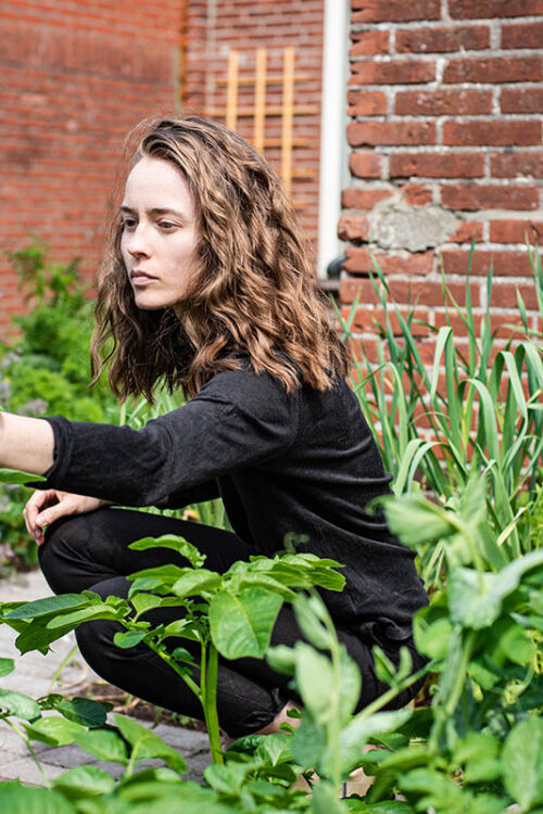 Woman crouching down to garden, wearing all black, with potato plants in foreground.