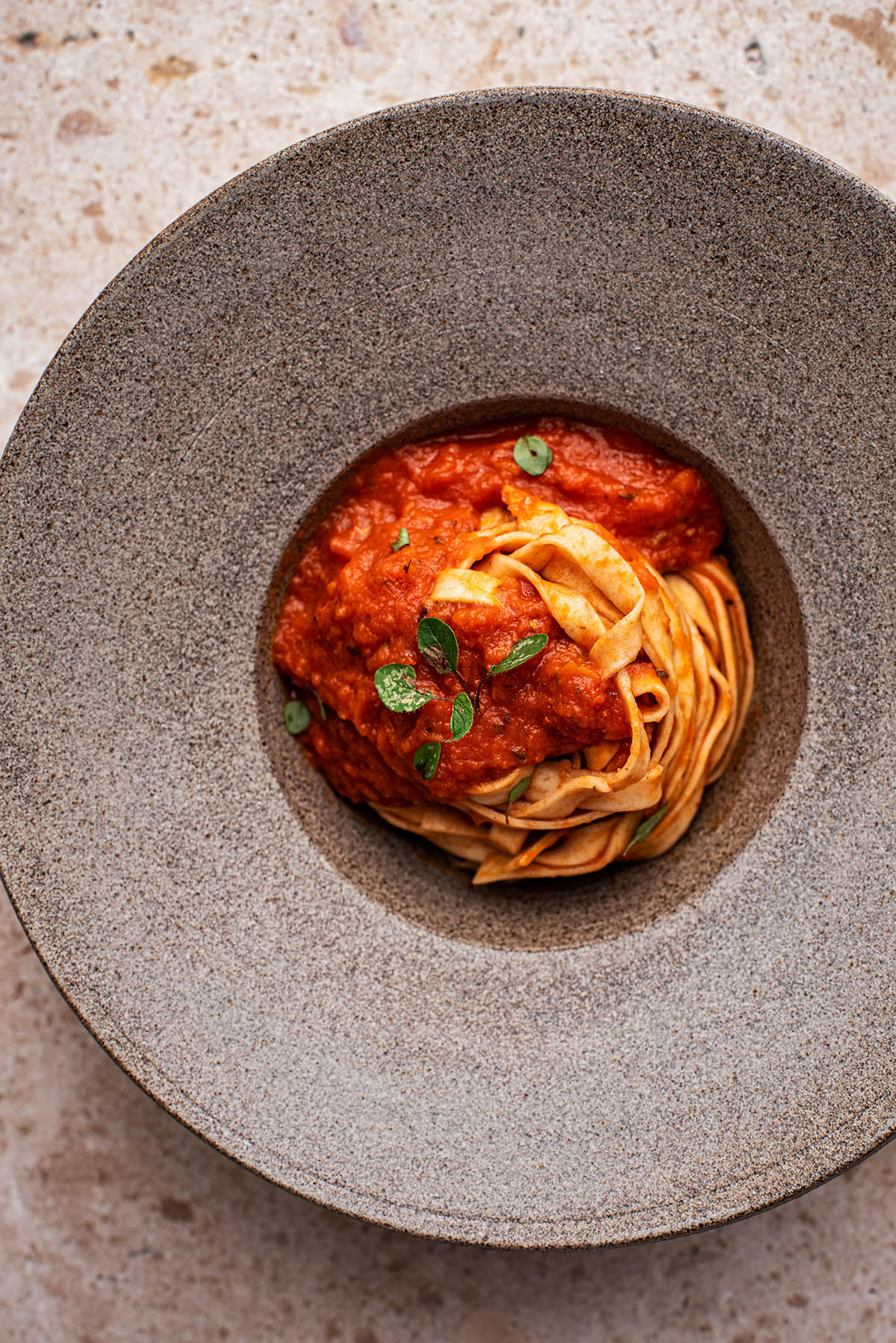 Linguine in a bowl with tomato sauce and oregano.