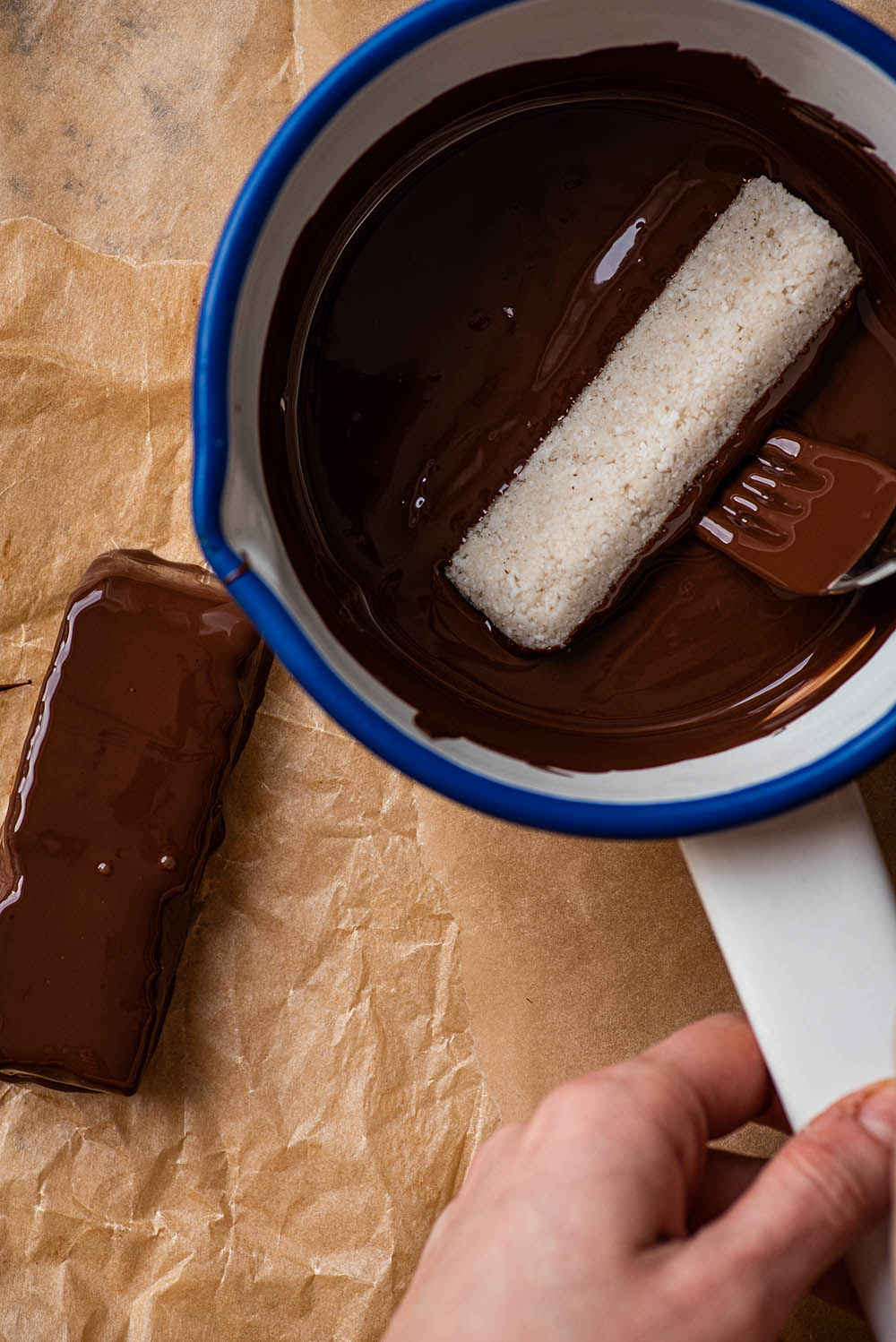 Dipping a coconut bar in melted chocolate.