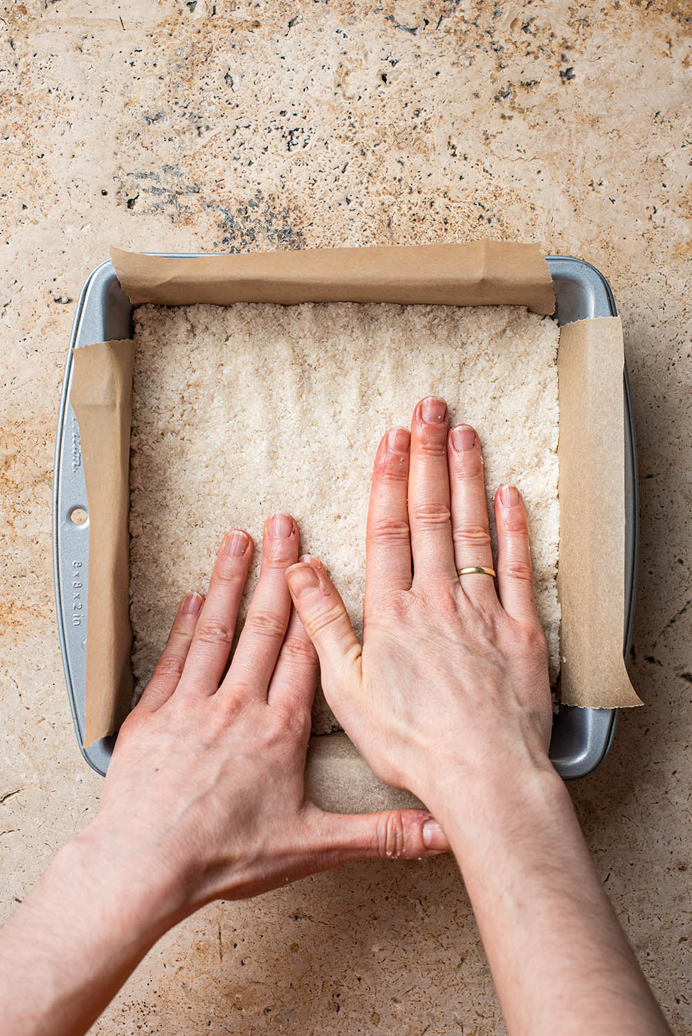 Woman's hands pressing coconut mixture into a square tin.