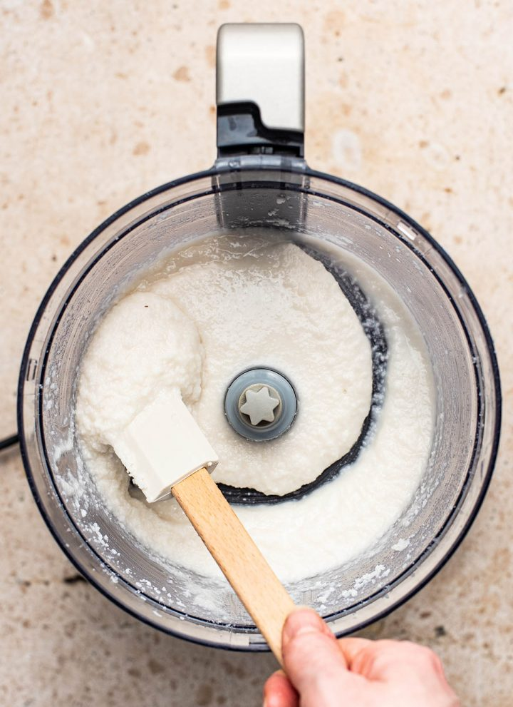 Finished coconut butter being moved with a spatula in the mixer.