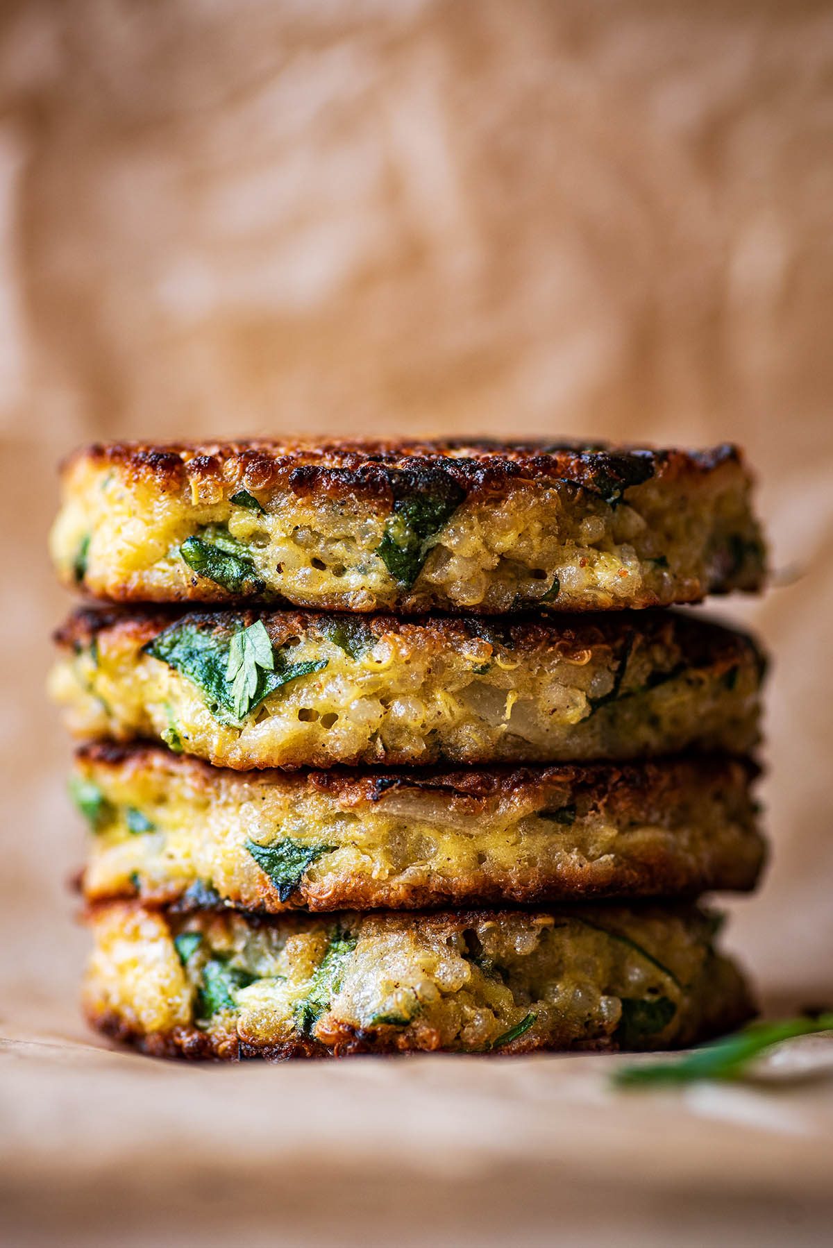 A stack of four quinoa patties on baking paper.