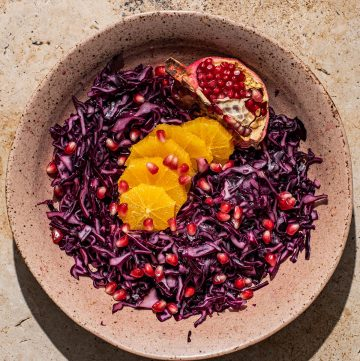 A shallow bowl of red cabbage salad with orange and pomegranate.