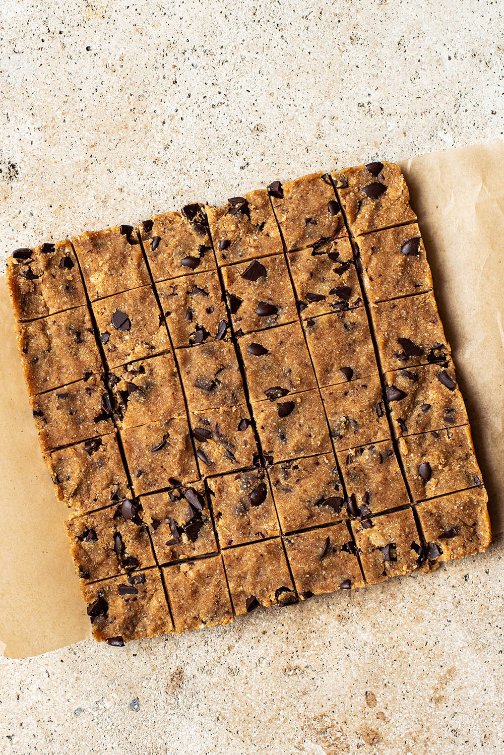 A slab of cookie dough cut into 36 small squares.