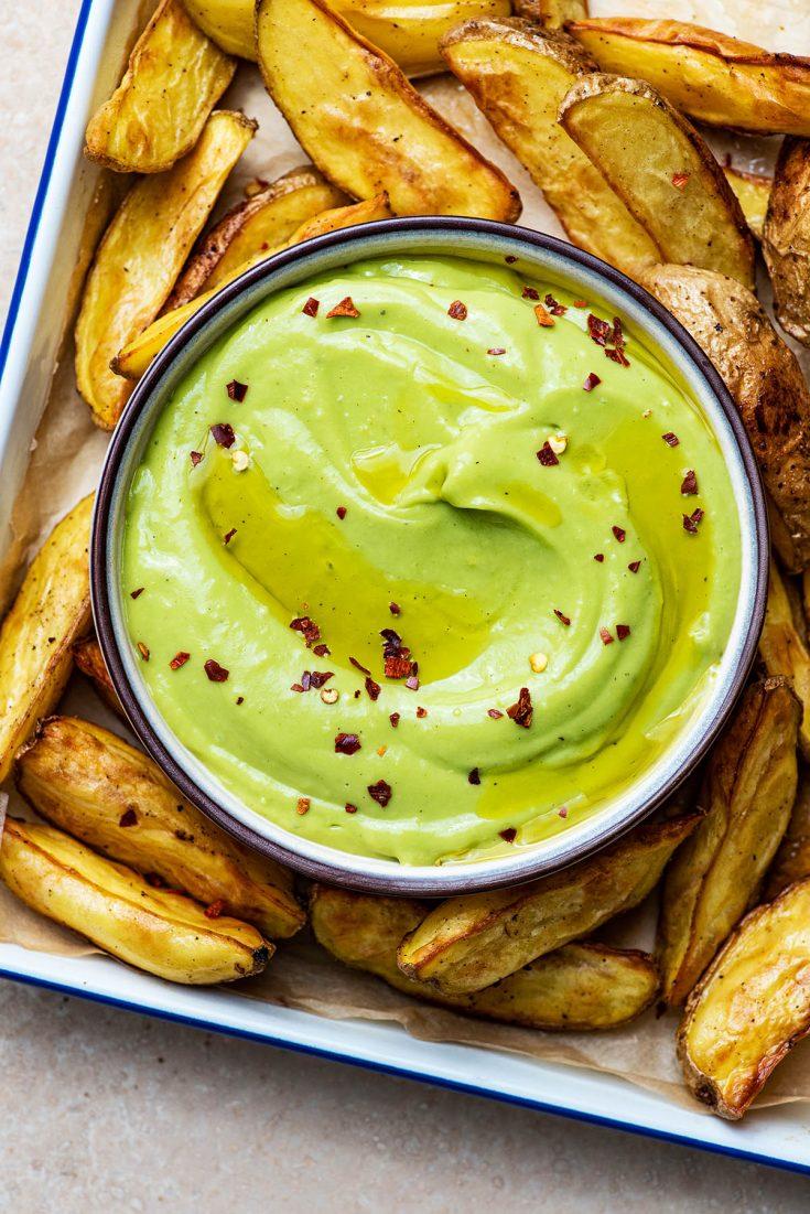A dish of avocado aioli with roasted potato wedges.