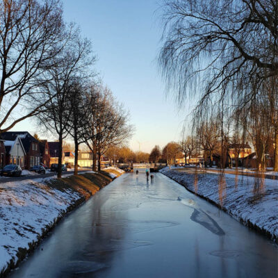 People skating on a frozen canal.