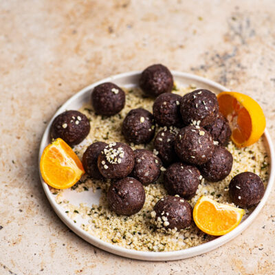 Hemp bites on a plate with more hemp and tangerine pieces.