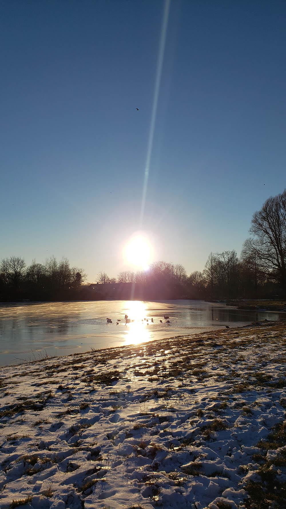 Sun over water at a human-made lake.