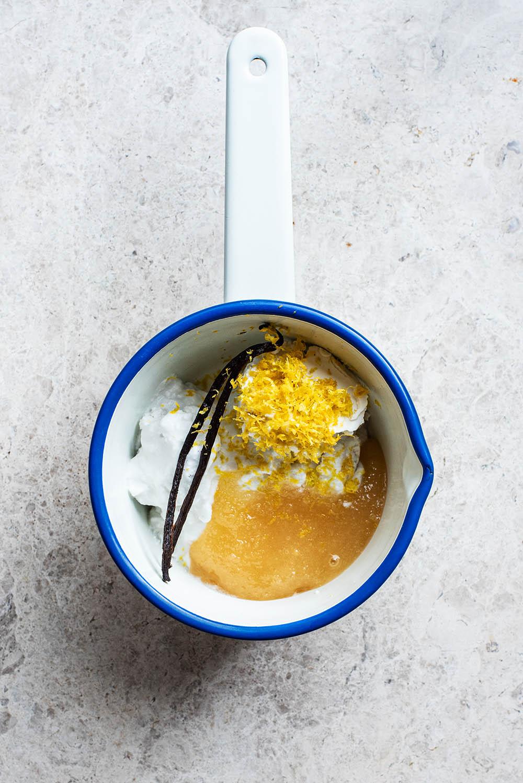 Coconut cream, vanilla, honey, and lemon zest in a saucepan.