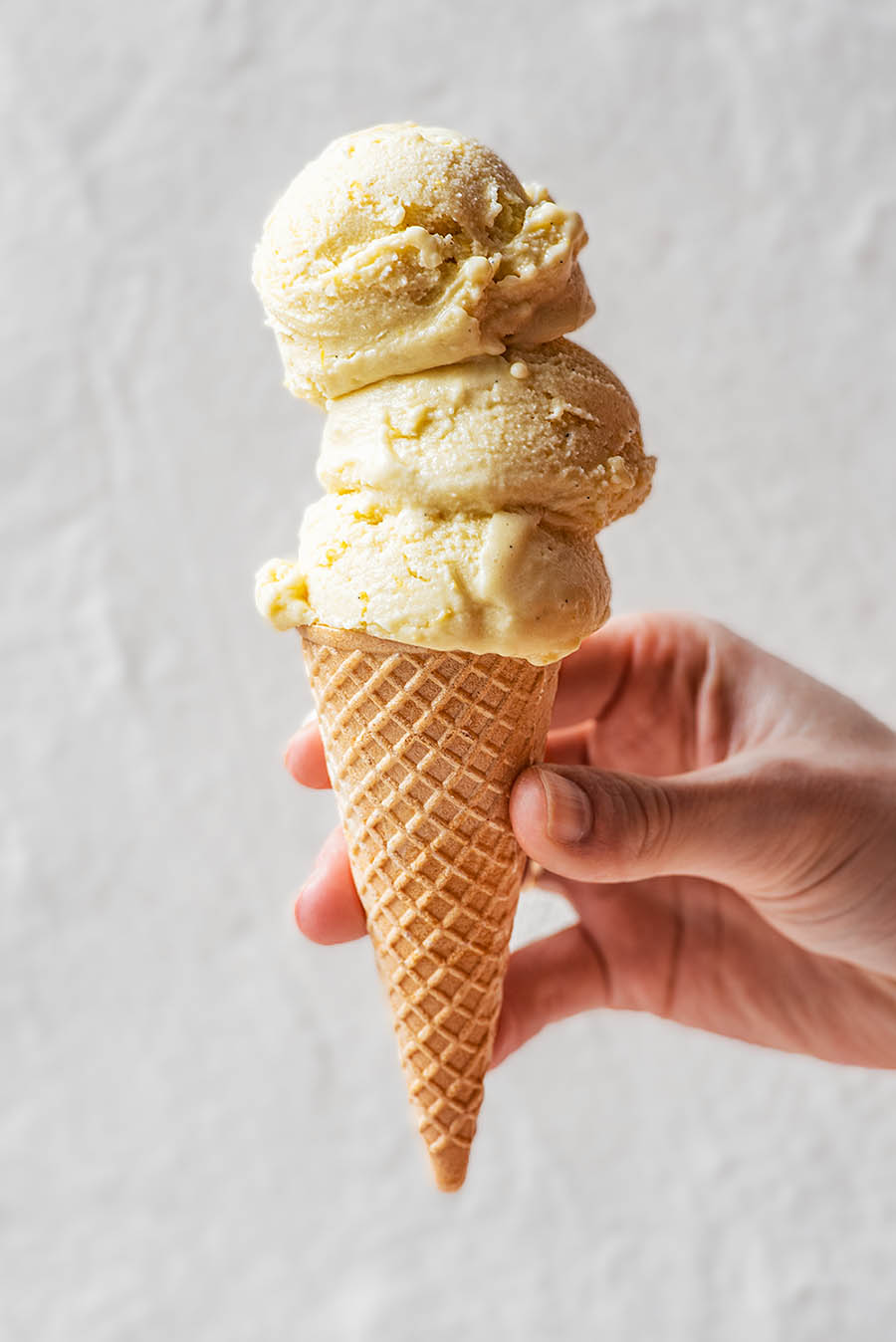 Hand holding a cone with three scoops of ice cream.