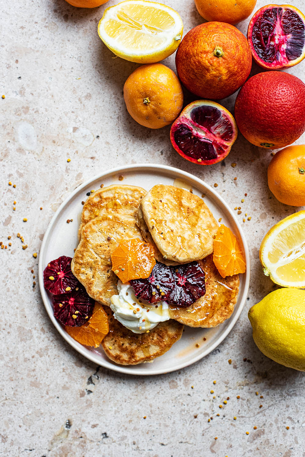 Several pancakes on a plate with citrus fruits around.