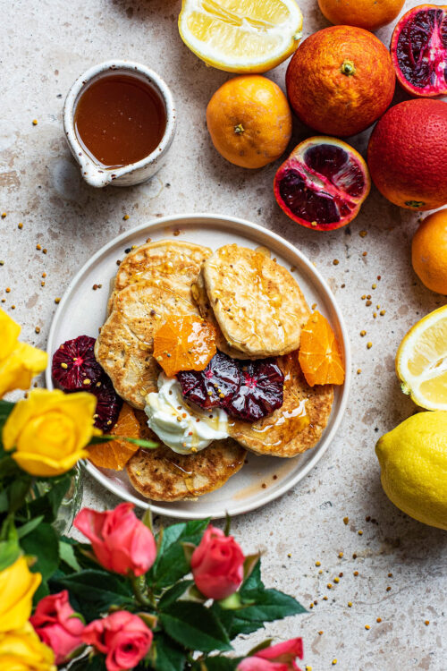Lemon pancakes on a plate with roses and citrus fruits around.