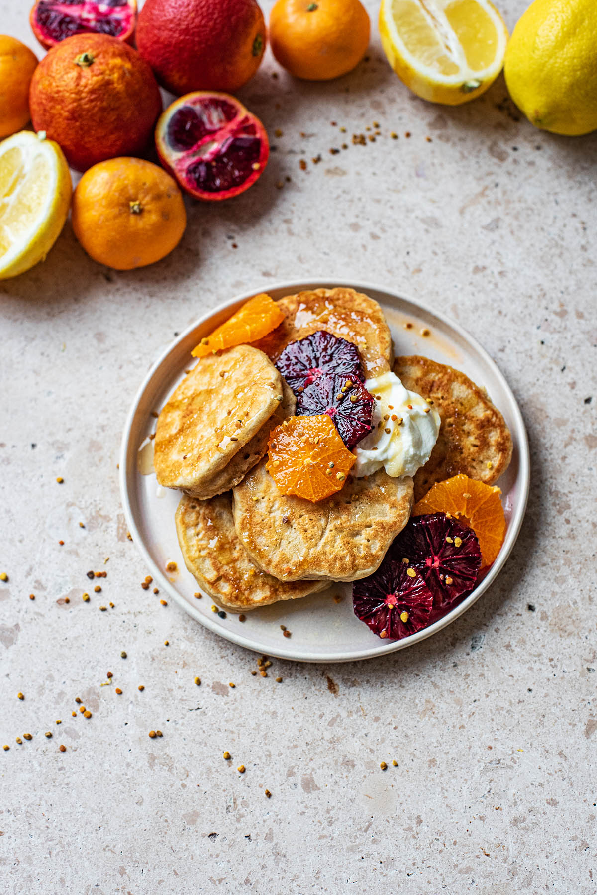 A plate of pancakes with yogurt and orange slices.