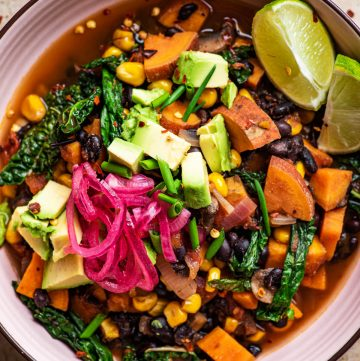 Close up of a bowl of sweet potato chili with avocado and pickled onion.