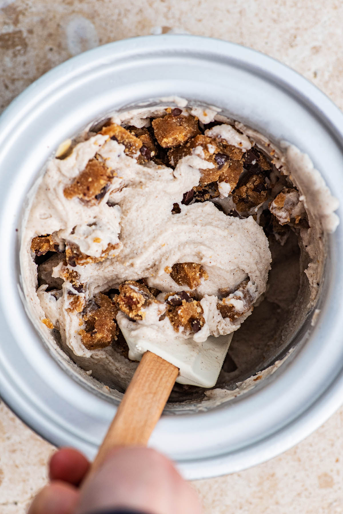 Stirring bits of cookie dough into the ice cream.
