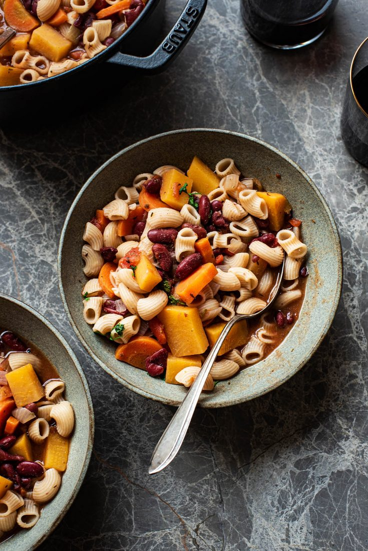 A bowl of minestrone with a spoon.