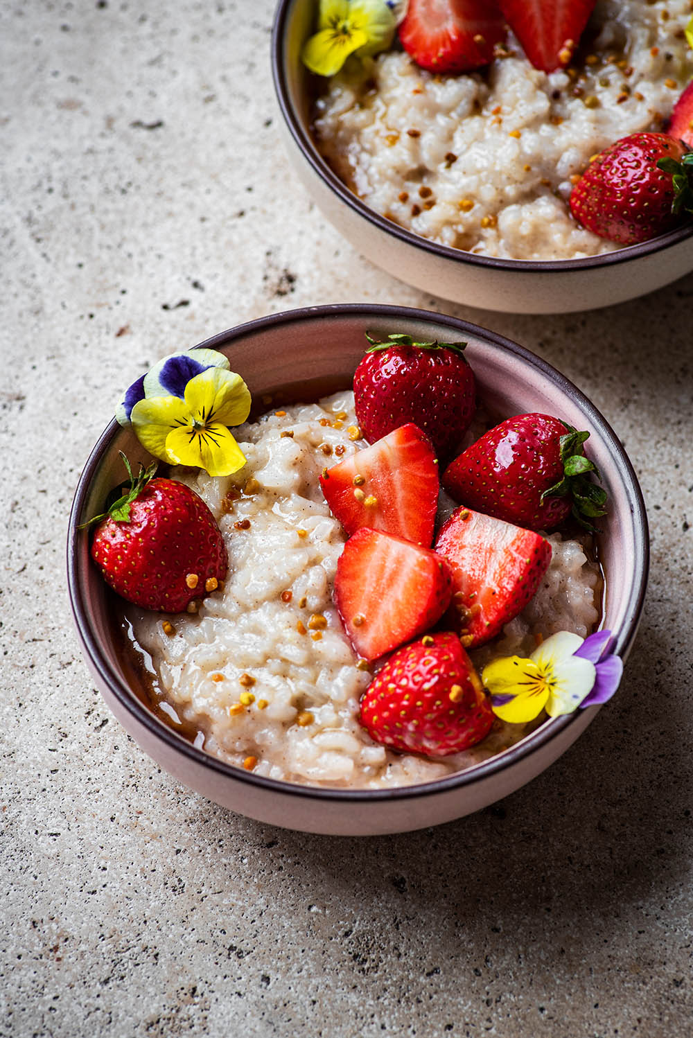 Two small bowls of rice pudding topped with strawberries.
