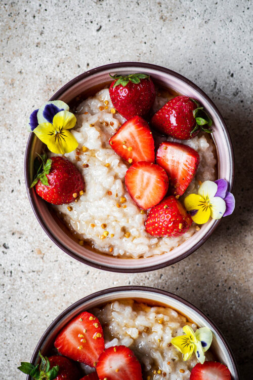 Two bowls of rice pudding, one half in shot, with berries.