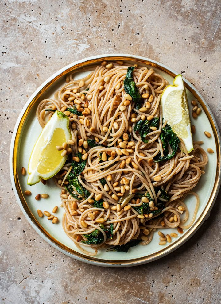 Large plate of spaghetti with spinach, garlic, lemon, and cedar nuts.