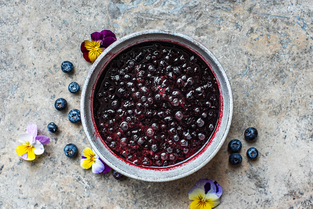 Blueberry compote in a small bowl with fresh berries and pansies around.