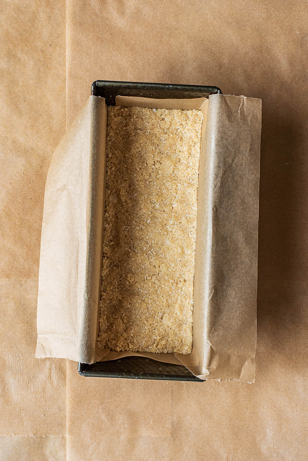Base layer pressed into a lined loaf tin.
