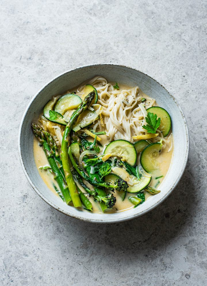 Rice noodles and green vegetables in coconut milk broth.