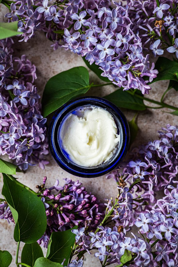 Finished deodorant in a small jar surrounded by lilacs.