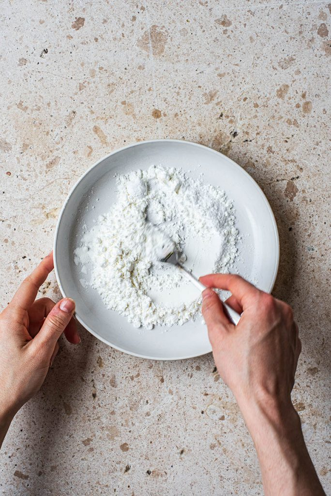 Woman's hands mixing the powders in a shallow bowl.
