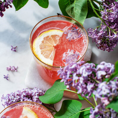 Two glasses of lilac lemonade with ice cubes, lemon slices, and lilacs.