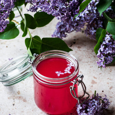 A glass jar of lilac syrup surrounded by blossoms.