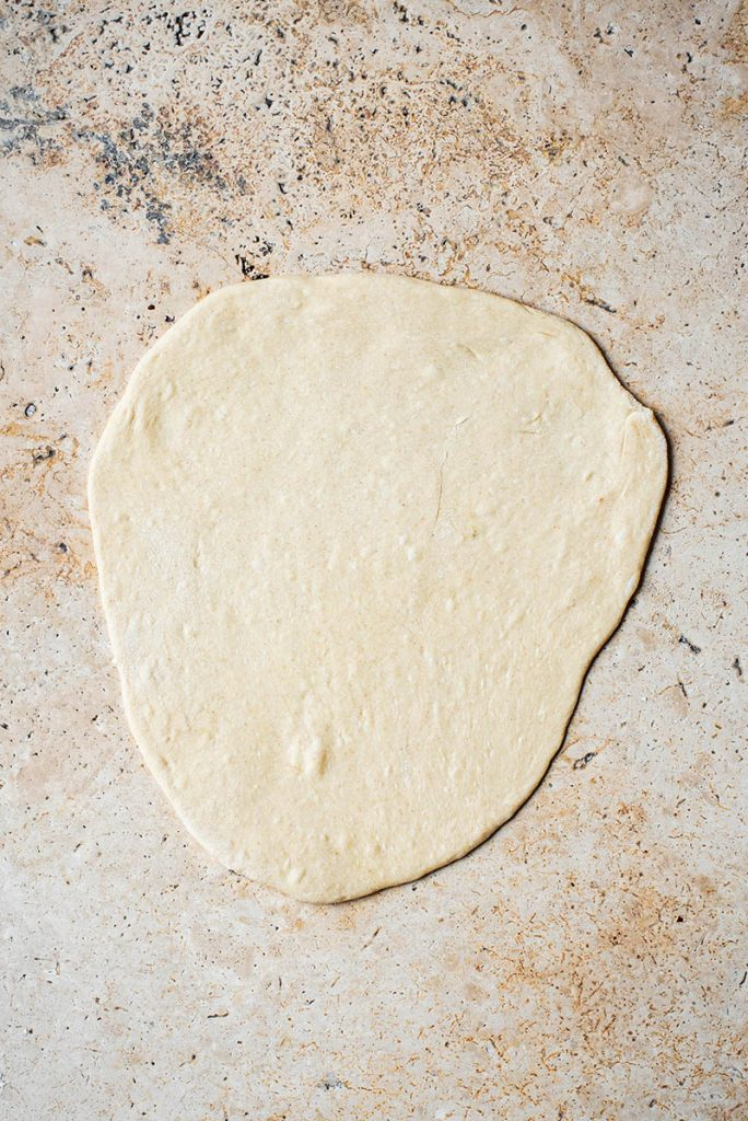 Bread dough rolled out before cooking.