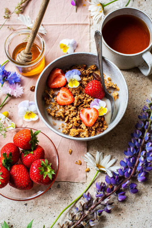 Front angle view of a bowl of granola with strawberries, tea in background and flowers around.