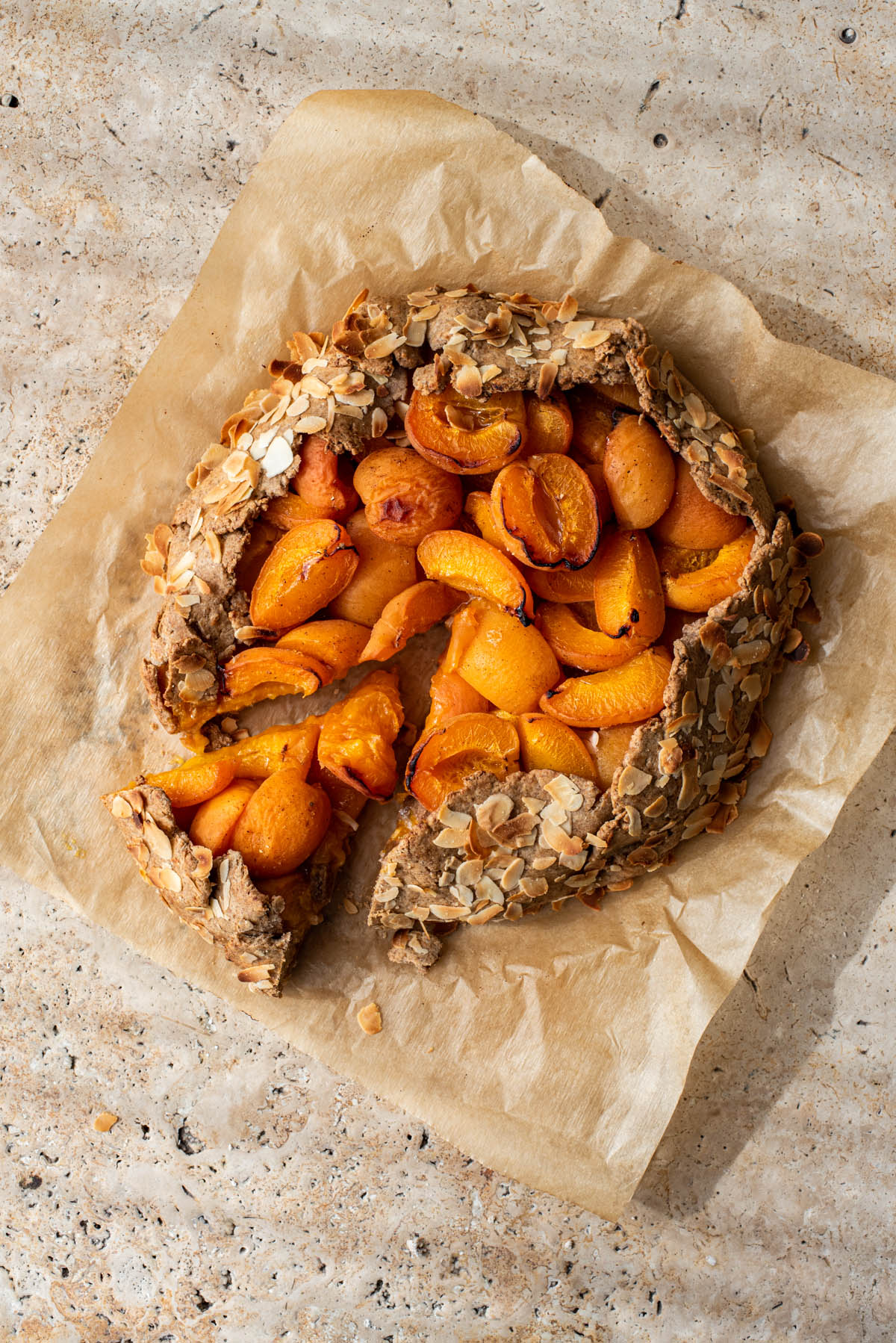 Apricot galette on parchment paper with one slice cut, in dappled sunlight.