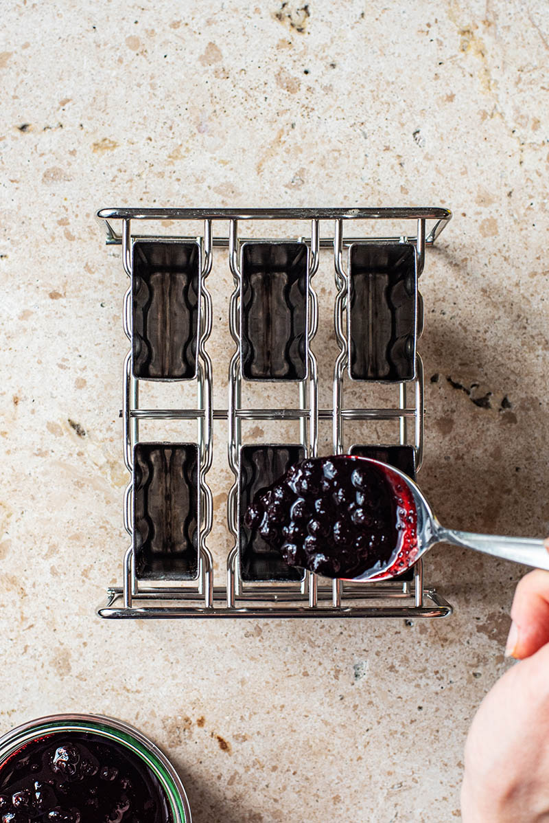 Adding a spoonful of blueberry compote to a metal popsicle mould.