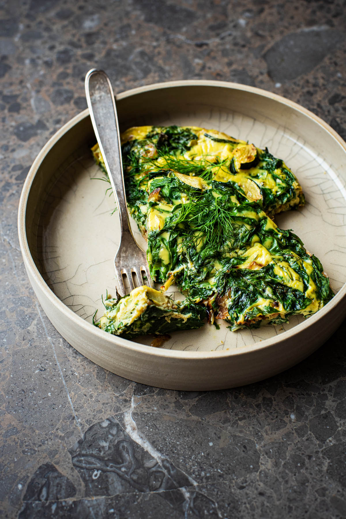 Two triangles of frittata in a deep plate with a piece speared onto a fork.