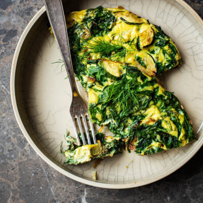 Two pieces of frittata in a deep place with extra herbs and a fork.
