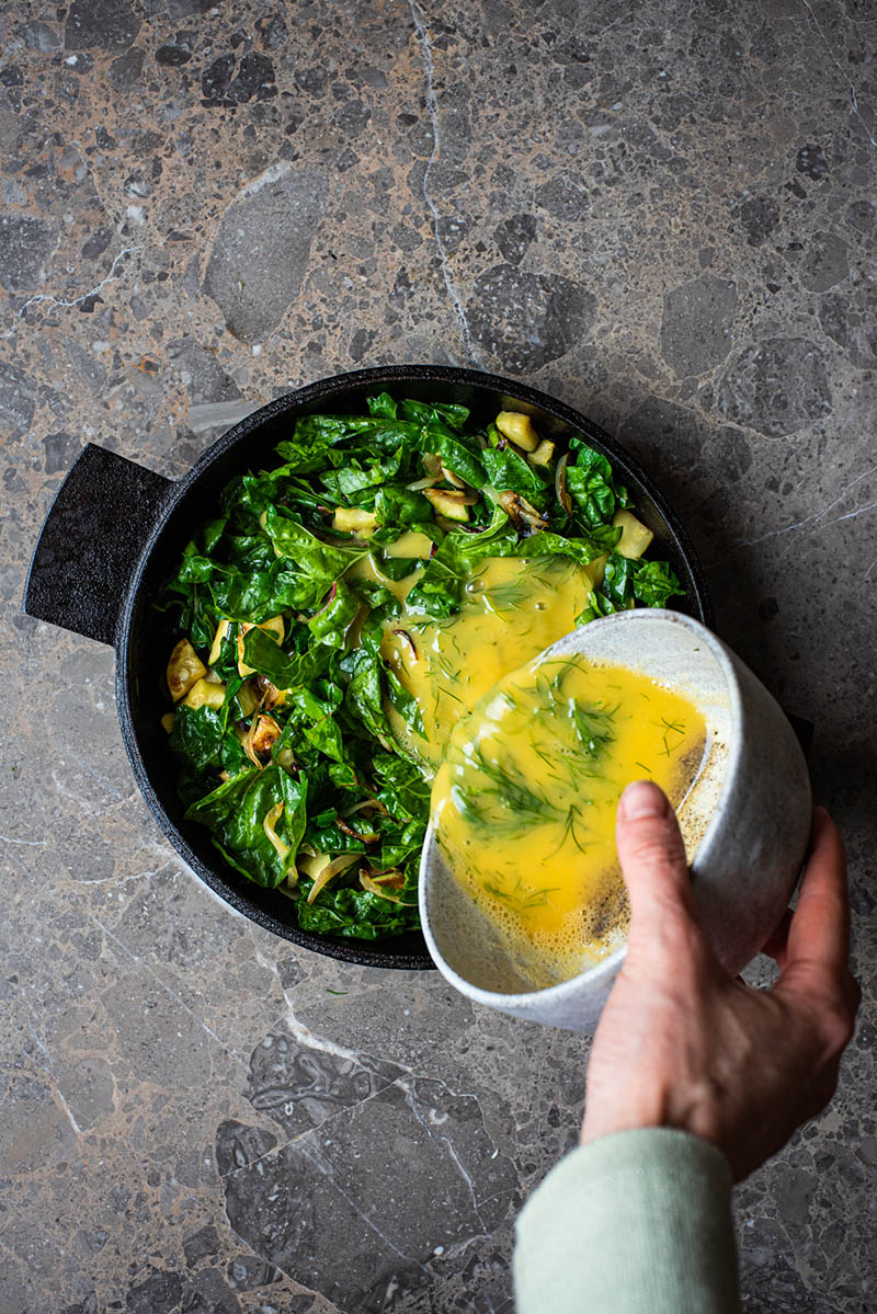 Woman's hand pouring the bowlful of whisked eggs into the pan.