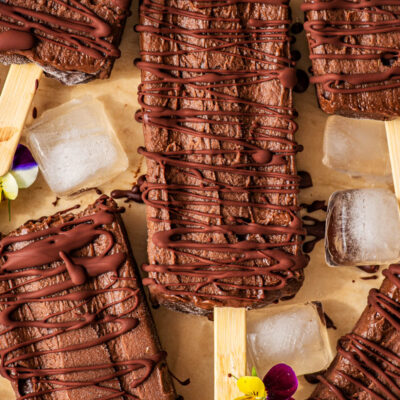 Fudgesicles drizzled with dark chocolate, with ice cubes and pansies.