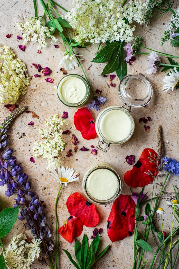 Three small jars of cream surrounded by wildflowers.