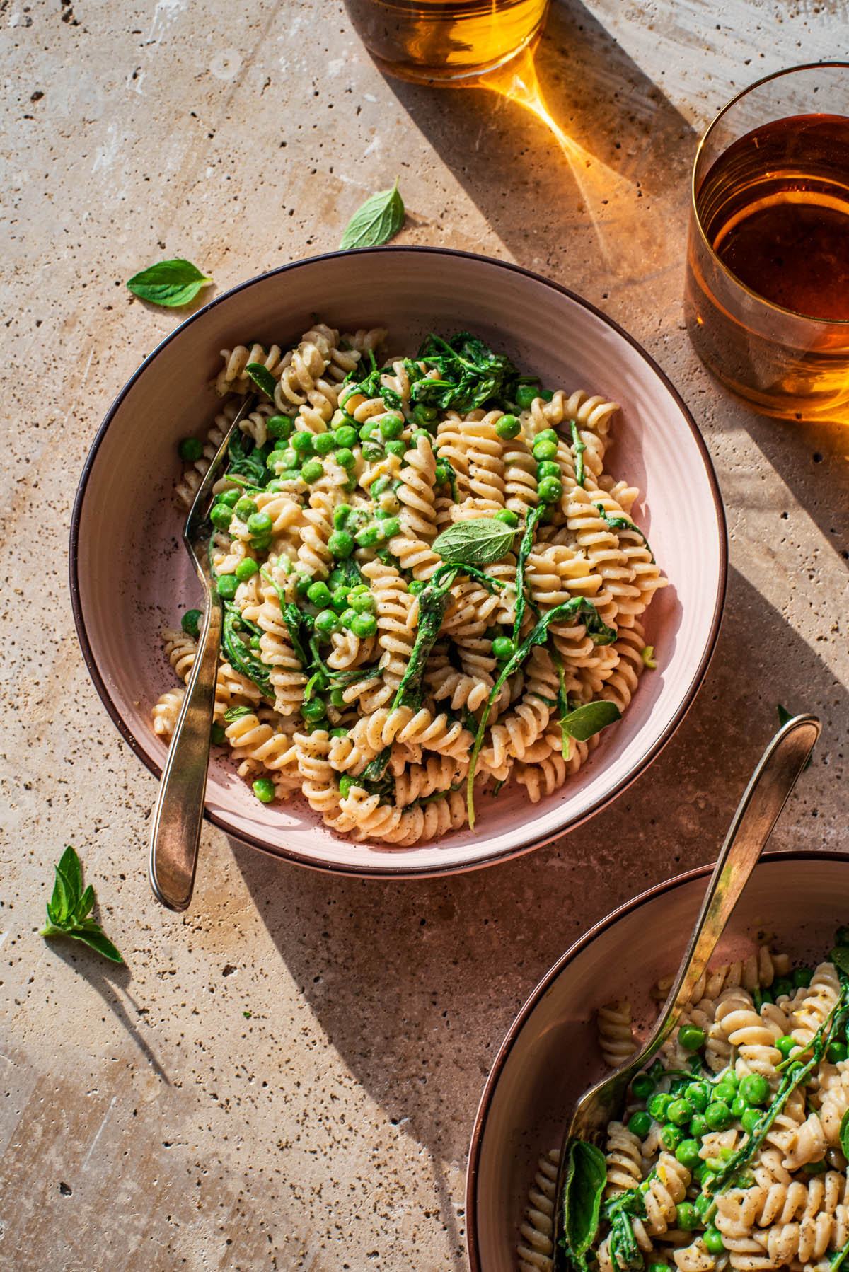 Two bowls of pasta with peas and greens.