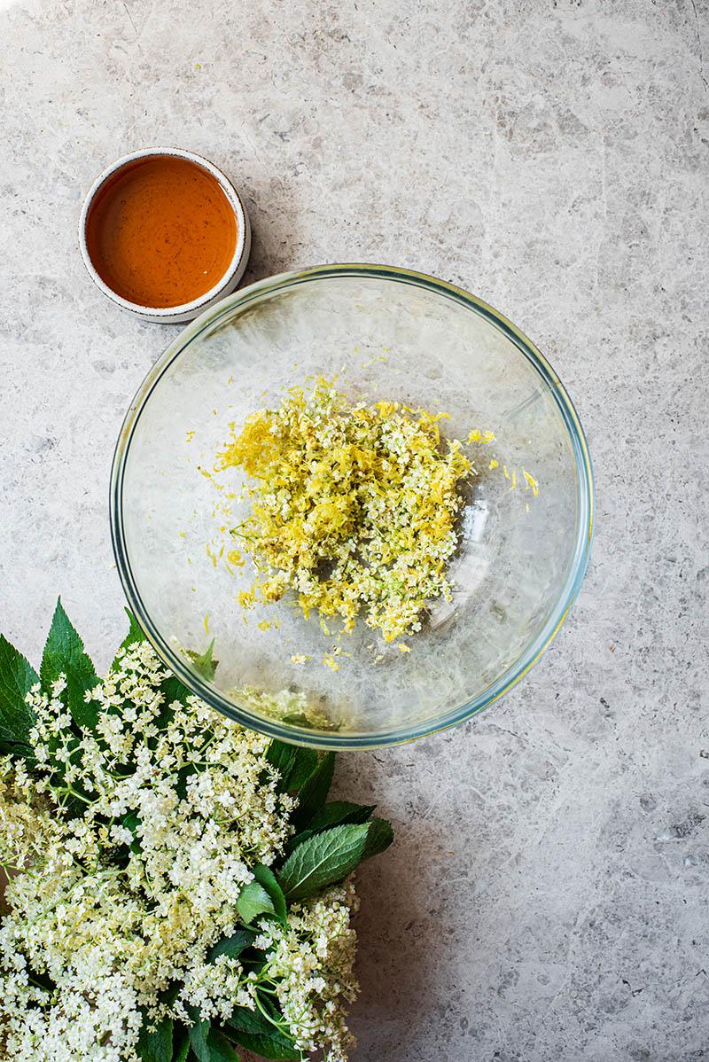 Elderflower blossoms, lemon zest, and ginger in a bowl.