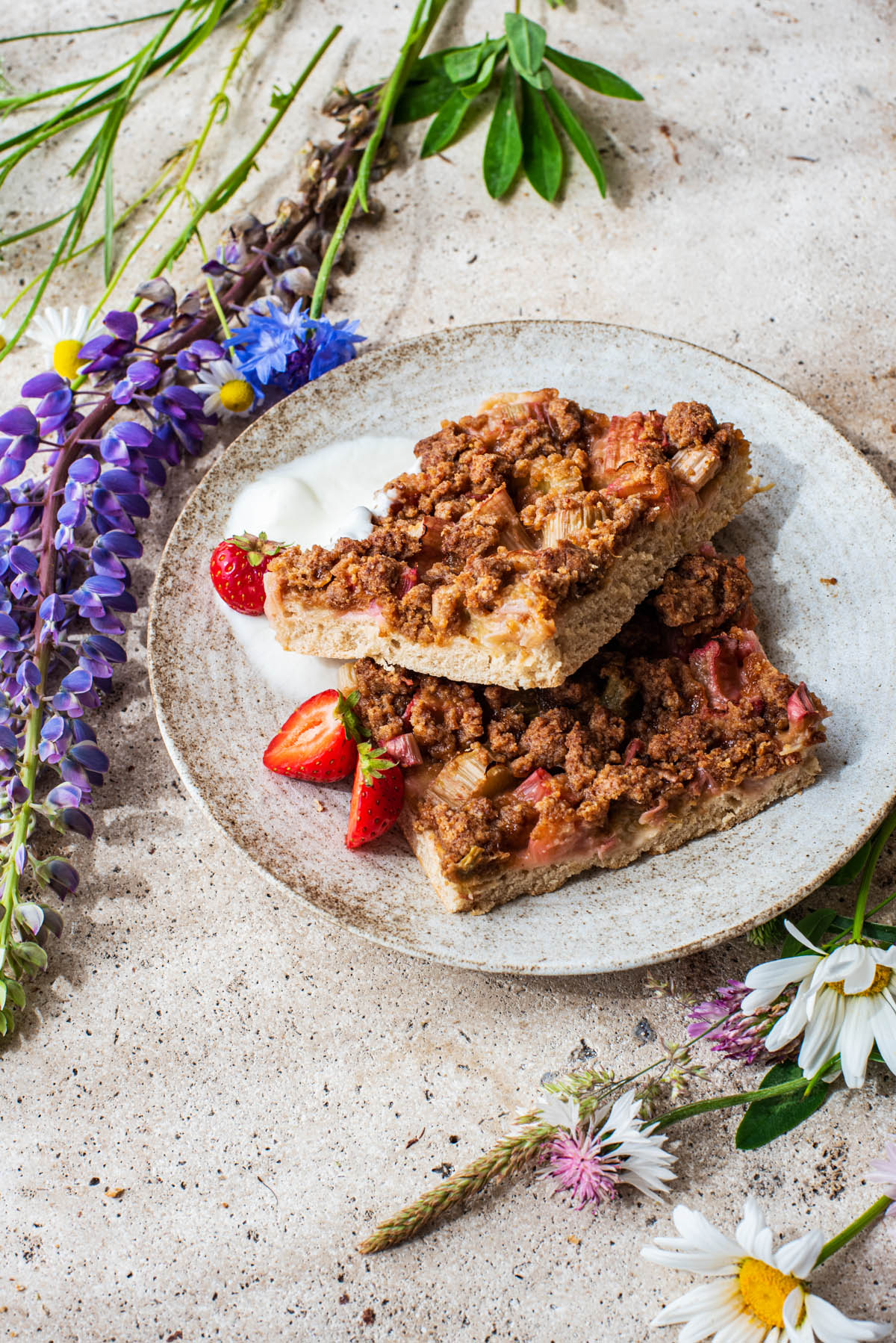 Two pieces of cake on a plate with wildflowers around.