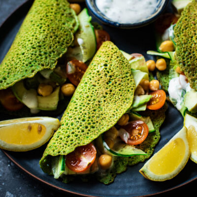 Filled spinach pancakes with lemon wedges and yogurt sauce.