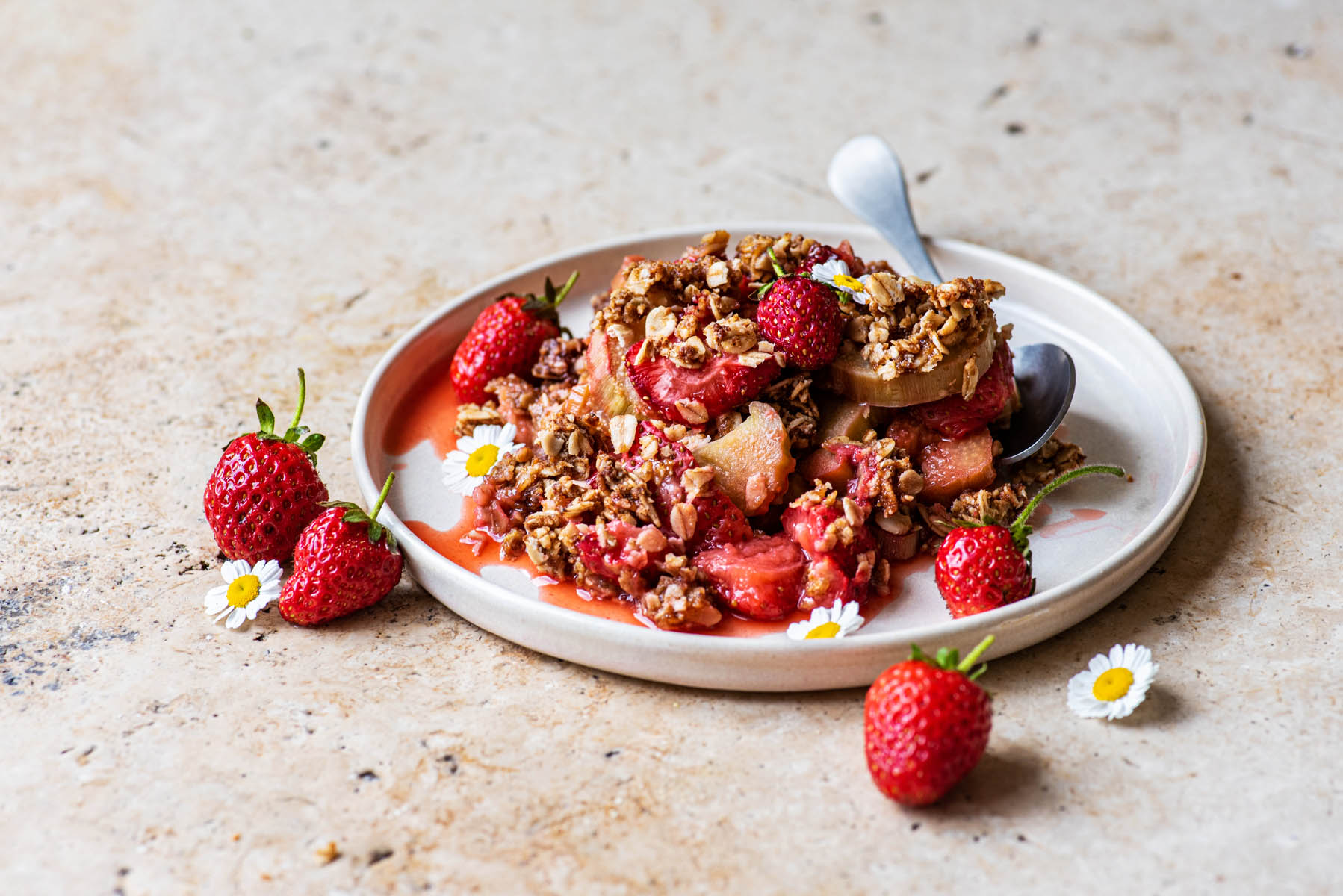 Rhubarb crisp on a small plate with a spoon and fresh berries.