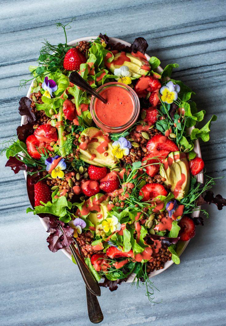 Salad on a platter with vinaigrette added.