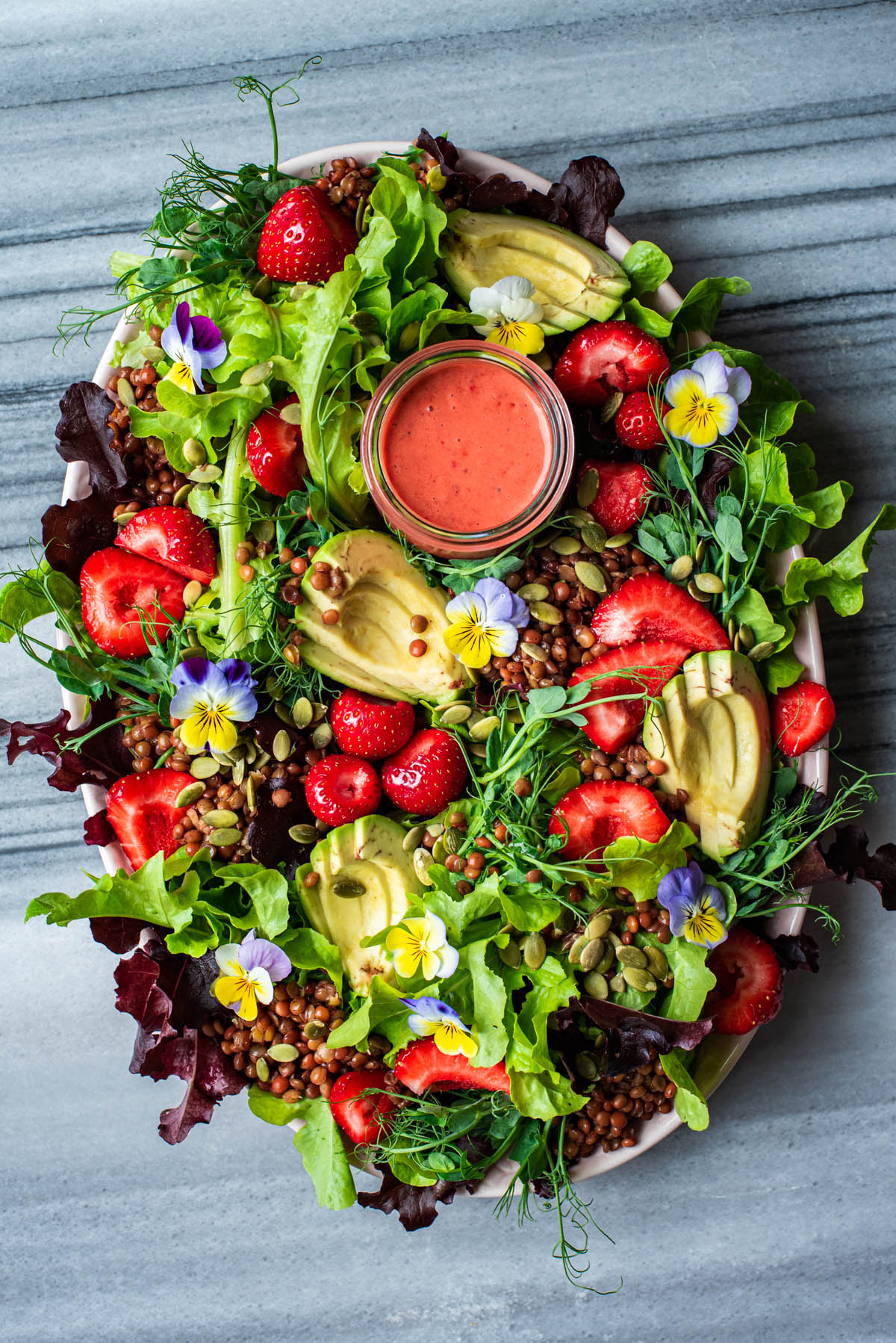 Strawberry salad with edible flowers, avocado, and lentils on a large platter.