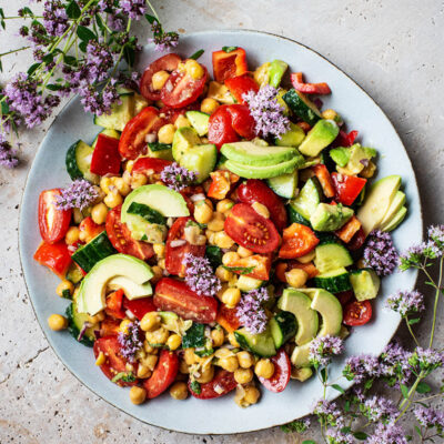 A platter filled with chickpea salad with tomatoes, avocado, and other summer vegetables.