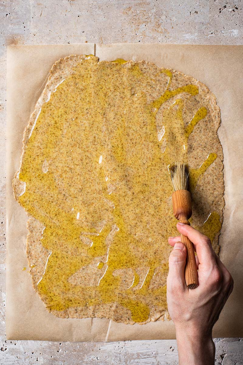 Brushing rolled out dough with olive oil.