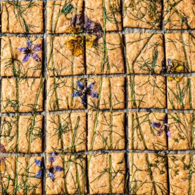 Baked crackers topped with edible flowers and herbs, cut into small squares.