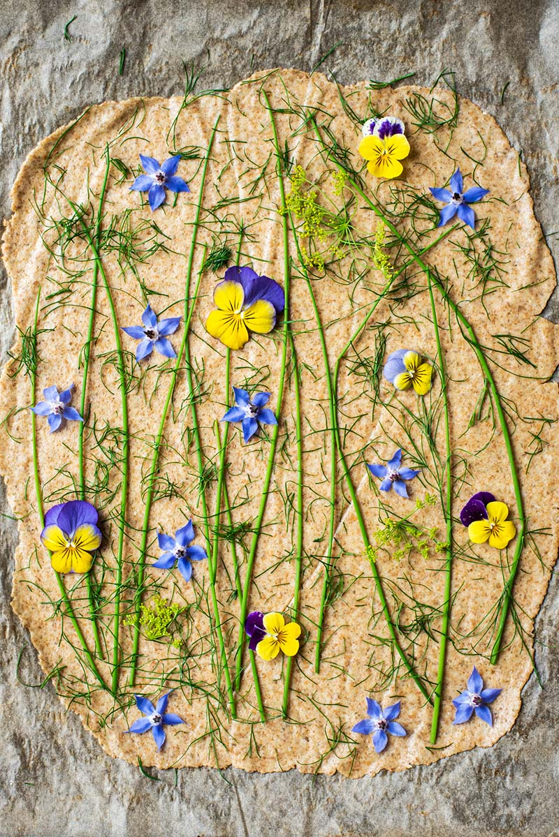Cracker dough topped with edible flowers and herbs before rolling.